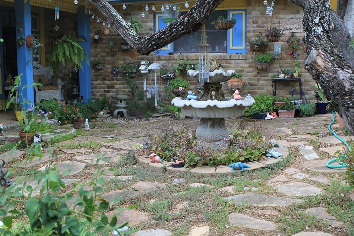 backyard stone area full of personality, fountain and plants