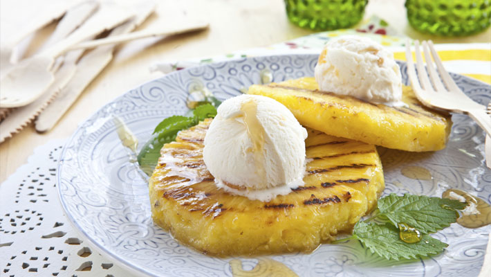 grilled pineapple with ice cream on top and mint leaves and syrup