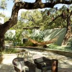 Shady patio with hammock and table area.