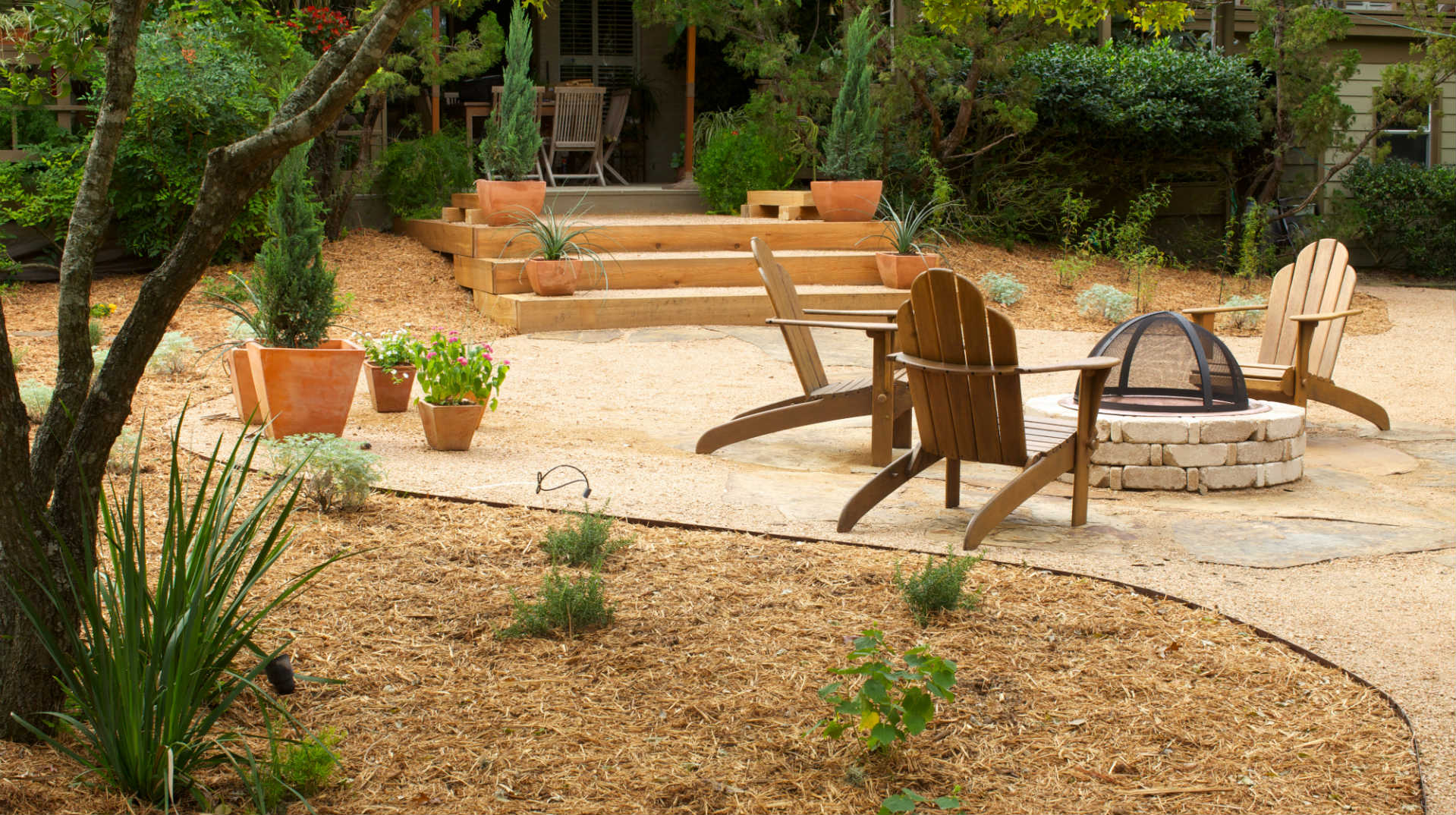 Backyard with clean lines and patio with firepit.