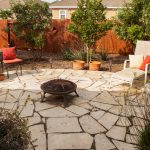 Flagstone patio with firebowl expands backyard living space.